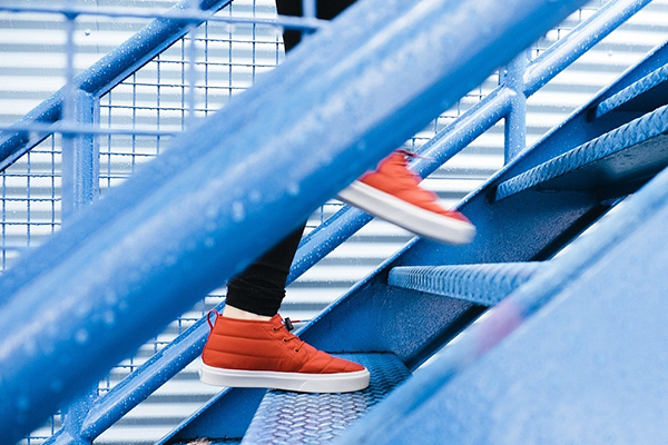 Close-up of feet climbing a flight of stairs